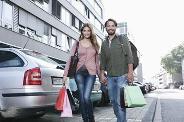 Deutschland, Köln, Junges Paar mit Einkaufstüten in der Nähe Parkplatz