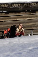 Frau entspannt vor Almhütte