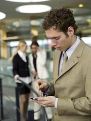 Junger Geschäftsmann mit Handy, Frauen reden im Hintergrund
