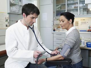 Deutschland, Hamburg, Doktor, der den Blutdruck des Patienten prüft