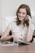 Deutschland, München, junge Frau im Büro mit Handy