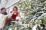 Österreich, Land Salzburg, Flachau, Junger Mann und Frau schmücken Weihnachtsbaum im Winter