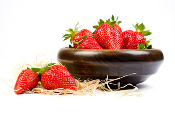 Strawberries in a wooden bowl on a white background