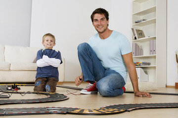 Vater und Sohn spielt mit Spielzeug-Rennstrecke