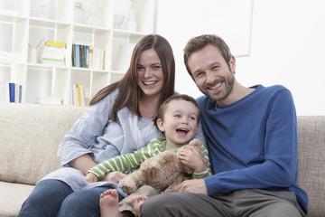 Deutschland, Bayern, München, Familie auf dem Sofa im Wohnzimmer