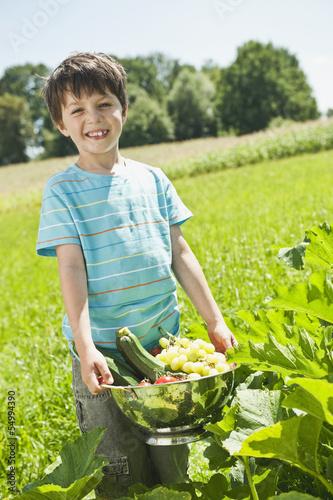 Deutschland, Bayern, Junge hält Gemüse im Garten, Lächeln