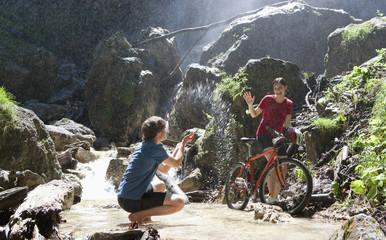 Österreich, Salzkammergut, Mondsee, Junges Paar mit Fahrrad und Wasserfall im Hintergrund