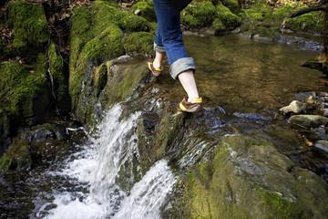Junge Frau läuft über kleinen Wasserfall