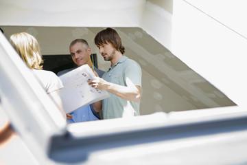 Junges Paar und Architekt debatieren auf der Baustelle