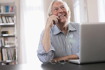 Deutschland, Wakendorf, erwachsener Mann am Telefon mit Laptop