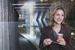 Deutschland Bayern, München, Geschäftsfrau im U-Bahnhof hält Pappbecher