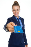 Closeup on credit card in hand of smiling business woman