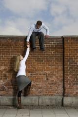 Deutschland, Bayern, München, Junger Mann helfen junge Frau, eine Mauer zu klettern