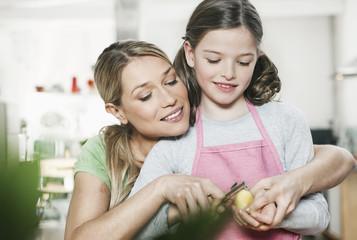 Deutschland, Köln, Mutter und Tochter schälen Kartoffel
