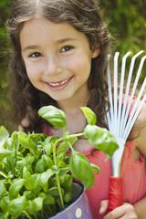 Deutschland, Bayern, Mädchen mit Topfpflanze und Harke