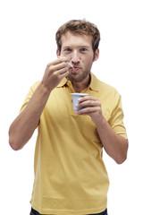 Junger Mann isst Joghurt