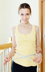 Happy ordinary girl measuring waist