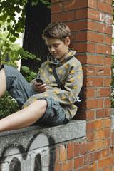 Deutschland, Berlin, Junge sitzt gegen die Wand mit Handy