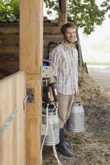 Bauer trägt Milchkannen