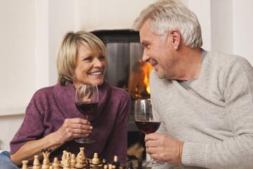Deutschland, Kratzeburg, älteres Paar, Senioren mit einem Glas Wein und Schachbrett