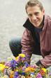 Deutschland, Bayern, München, Mann hockend vor Blumen, Lächeln