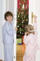 Mädchen und Jungen stehend an der Tür beobachten Weihnachtsbaum