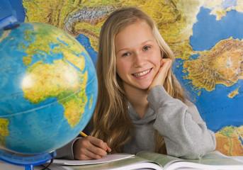 Teenager-Mädchen schreibt auf Buch mit Globus, Lächeln
