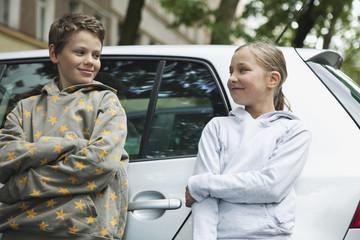 Deutschland, Berlin, Junge und Mädchen lehnen an Auto