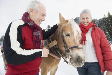 Italien, Südtirol, Seiseralm, älteres Paar, Senioren stehend vor Pferd, Lächeln
