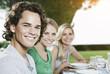 Italien, Toskana, Magliano, Junger Mann und Frau an Esstisch, Lächeln