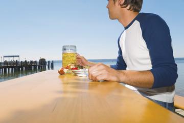 Deutschland, Ammersee, Junger Mann draußen essend