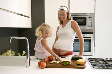 Schwangere Mutter und Tochter in der Küche