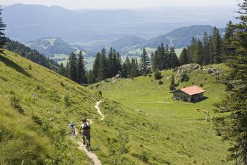 Deutschland, Bayern, Chiemgau, Zwei Männer Mountainbiken über Berglandschaft