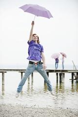 Deutschland, Bayern, Ammersee, Junger Mann mit Regenschirm und springend