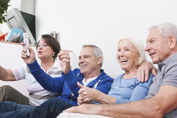 Deutschland, Leipzig, Ältere Männer und Frauen sitzen auf Couch