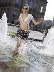 Teenager-Mädchen Spritzwasser in Brunnen