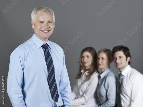 Ein Mann und zwei Frauen schauen einen Mann an, der lächelt