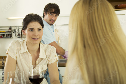 Drei junge Leute trinken Wein in der Küche