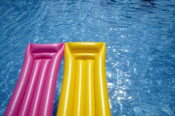 Zwei Luftmatratzen schwimmen im Pool rum