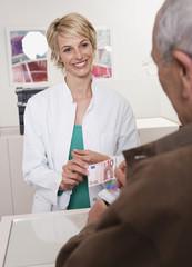 Deutschland, München, Mann mit Versicherungskarte, Arzt