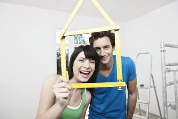 Deutschland, Köln, Junges Paar, das Haus-Modell Tasche Zollstock vor ihnen