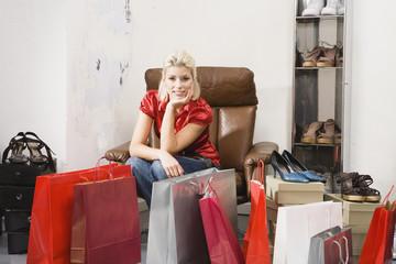 Junge Frau im Schuhgeschäft, Einkaufstaschen im Vordergrund