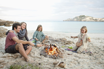 Spanien, Mallorca, Freunde grillen Würstchen am Lagerfeuer am Strand
