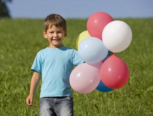 Junge auf Wiese mit Luftballons