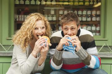 Deutschland, Bayern, München, Junges Paar am Viktualienmarkt mit Snack