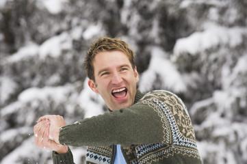 Italien, Südtirol, Junger Mann mit Schneeball, lachend