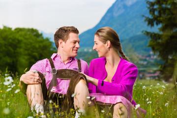 Paar in Tracht auf Wiese vor Alpen Panorama