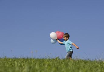Österreich, Mondsee, Junge rennt mit Luftballons durch Wiese
