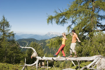 Junges Paar Balancieren auf gefallenen Baumstamm.