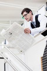 Deutschland, Bayern, Diessen am Ammersee, Geschäftsmann lehnt am Geländer und liest Zeitung